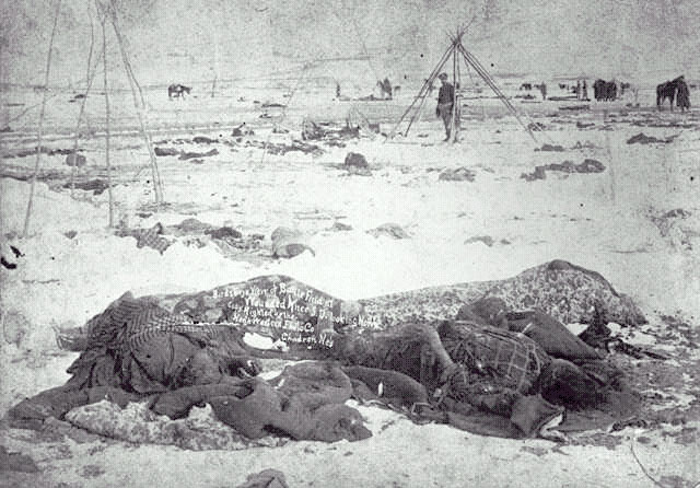 Frozen bodies being removed at wounded knee